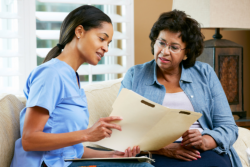 Caregiver is explaining some documents to the old lady